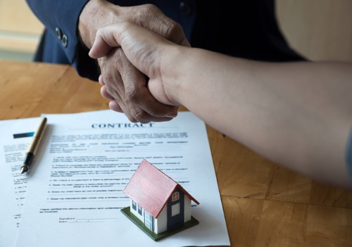 A client shaking hands with a lawyer over a housing contract during Real Estate Law in Monmouth IL