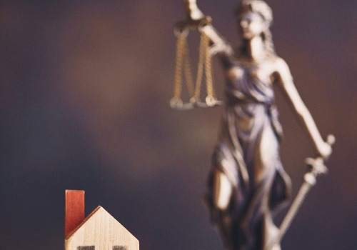 Block House and Lady Justice Sitting on the Desk of a Lawyer Who Handles Property Disputes in Monmouth IL
