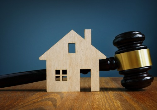 A wooden model of a house next to a gavel, representing real estate law in Galesburg IL
